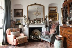 Giant gold mirror, vintage paintings, mismatched chairs ... so much to love in this room!  via Period Living.