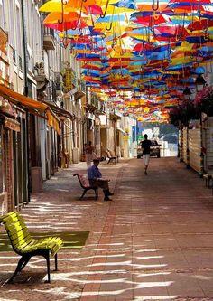 """Portugal : les parapluies multicolores d'Águeda, Une installation composée de parapluies multicolores suspendus au ciel dans les rues commerçantes de la ville pour rafraîchir les badauds durant les mois d'été. ça mérite d'y laisser un message surprise : """"Ferme la bouche quand tu regardes en l'air, tu vas gobber une mouche ! """""""