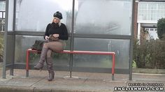 Sexy blonde British woman in short shirt and fishnet pantyhose tights and leather boots flashing her legs and thighs I the street.