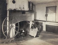OLDEN TIMES. Middle aged woman watching her cooking from a rocking chair by a fireplace as she smokes a pipe. Photograph made in 1900, recreating the frontier lifestyle of the early 19th century.