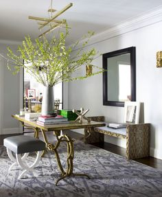 The foyer of Ashley Stark Kenner's New York apartment, designed by James Aman and John Meeks, is a study in gold and silver, with an ikat rug from the Noor Collection providing the cooler tone and predominant pattern.