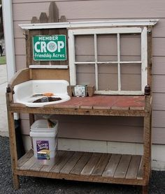 Potting bench made from wood pallets, a window, and an old sink