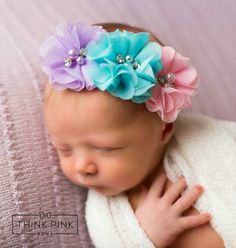 Our unique baby headband features 3 pastel organza flowers on a comfortable elastic headband. Each flower is topped with faux pearls and rhinestones. SHOP newborn headbands at http://thinkpinkbows.com/products/make-believe-floral-headband | Shabby Chic | Baptism | Spring + Summer | Vintage
