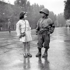 "The US Military Police adopted this Italian orphan boy of fourteen as their mascot. He mimics his adult comrades even to having a "" Girl-Friend "" ( SGT Wooldridge, Firenze, 7 september 1944 ) ~"