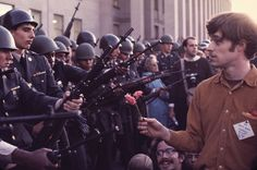 21 of 62 © Bob Adelman/Corbis  A peaceful anti-Vietnam War demonstrator holds up a flower to armed soldiers protecting the perimeter of the Pentagon. Photographed in 1968.