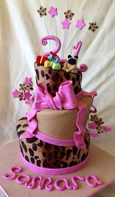 21st birthday cake, topsy-turvy style, leopard print on 2 tiers, with hot pink accents. Gumpaste pug-dog and tiny wrapped gifts on top. I can't wait till I'm 21.