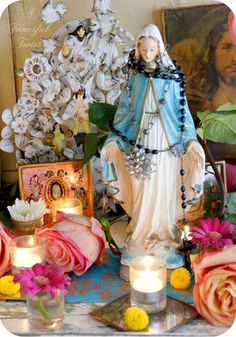 Lovely devotional home altar to the Virgin Mary with rosary beads, fresh flowers, candles, etc.