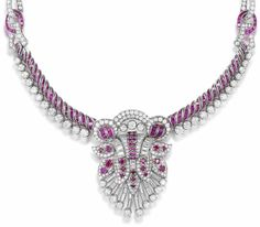 A ruby and diamond necklace, circa 1965  The calibré-cut ruby collar with brilliant-cut diamond fringe, suspending a central brilliant, single and baguette-cut diamond cartouche with circular and calibré-cut ruby highlights, on a calibré-cut ruby backchain, connected by ruby and diamond buckle motifs, diamonds approximately 15.95 carats total, length approximately 41.0cm