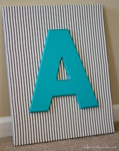 Create a simple monogram as wall decor for your child's room with just fabric and paint. This DIY wall art is the perfect way to add a splash of color and pattern to the wall!