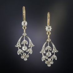 Lightly and lovingly hand fabricated in platinum over 18K gold, these darling Edwardian dangle earrings, dating back to the first or second decade of the twentieth century, are aglitter with a central old mine-cut diamond embellished all around with tiny twinkling rose-cut diamonds set in a graceful flowing foliate motif, swinging freely from a diamond stud. Delightful. Just over 1 inch long, they drop a bit further from the lever-back ear wires.