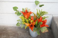 To use the orange-yellow palette of flowers, first build structure with greenery, using the vines and the goldenrod to fill out the vase and...