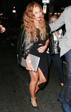 Beyoncé wears a sleek black dress with a cutout detail, leather motorcycle jacket, and black satin pumps