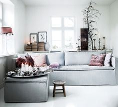 ale gray linen sofa with pastel accents looks so soft and cozy, via bolig magazine.