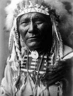 An imposing picture of Ghost Bear, a Crow Warrior. The picture was taken in Montana and shows the Indian in Full War Bonnet. It was created in 1908 by Edward S. Curtis. (BW copy)