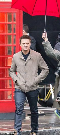 That's better: Renner kept his hands warm by burying them in the pockets of his jacket whi...