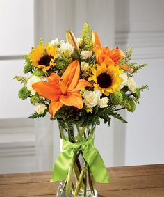 Mini sunflowers, orange Asiatic Lilies, yellow mini carnations, green button poms, yellow solidago, and lush greens are arranged perfectly in a classic clear glass vase tied at the neck with a lime green satin ribbon. #sunflowers #summerflowers #flowersofcharlotte