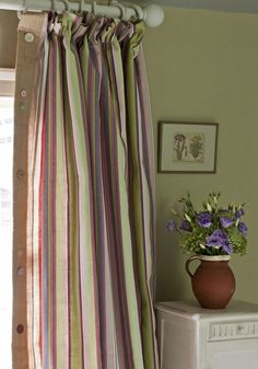 New for 2013 The Annie Sloan Fabric Collection™  The curtain is Gigi Ticking with a lining and fold around in Hessian/Burlap with assorted buttons against a versailles wall and Original/Old White painted side table with Clowers by Claire Chalkley of Couronnes Sauvages  in France.