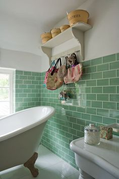 Claw foot bath and green brick tile wall in the bathroom