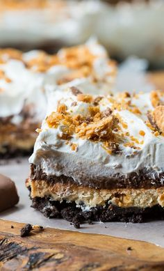Butterfinger Chocolate Lush has an oreo cookie crumb bottom, a peanut butter layer with crushed butterfingers, an chocolate pudding layer, and a Cool Whip topping.