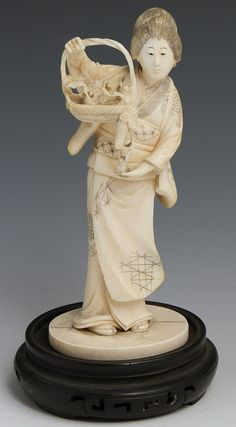 """JAPANESE CARVED IVORY OKIMONO OF GEISHA BEAUTY Japanese carved ivory okimono of Geisha beauty wearing traditional garb holding a basket of fruiting vines. Monochrome detail, unsigned. Adhered to ivory base. Weight: 164.7g Size: 5.5"""""""