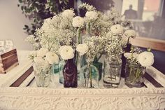 white ranunculus, baby's breath in vintage bottles, jars
