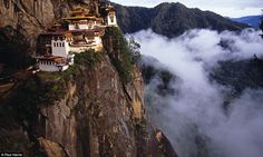 Closer to their god: The Taktshang Tiger's Nest monastery clings to a cliff 2,300ft above the Paro Valley floor in Bhutan at such a height it looks down on the clouds