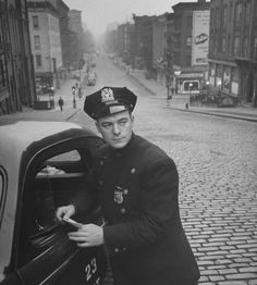 """103rd Street and Lexington Avenue. The caption to the photo reads: """"NYPD patrolman James Murphy standing by his 23 Precinct squad car on street of his East Harlem beat."""" It was taken in June 1948."""