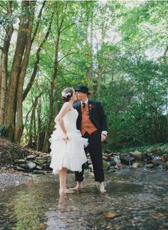 A bride and groom wading in Phillips Creek for their Smoky Mountain wedding at Hawkesdene House.