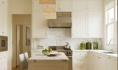 Carerra Marble backsplash and counter top in white kitchen by Stone Interiors, Remodelista