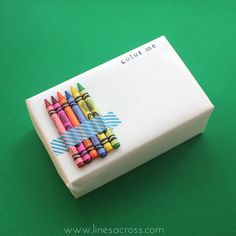 """Tape colorful crayons to a gift wrapped in plain white paper with the words """"COLOR ME"""" for a fun interactive gift wrap for kids."""
