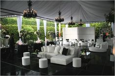 Outdoor reception under large tent for dancing, eating and drinking. Lounge seating located around the dance floor