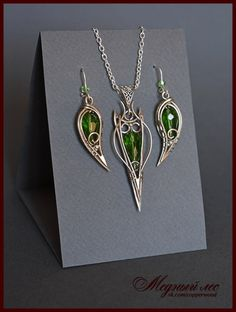 Комплект из нейзильбера с зеленой стеклянной бусиной.