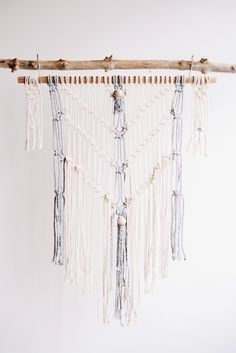 "This beauty is knotted onto a really cool square wooden hanger. Using beautiful gray rope in addition to the usual cream, this macrame wall hanging will look perfect in any room of the house. 36"" wide"