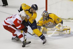 Nashville Predators goalie Pekka Rinne (R) stops the puck as his teammate Roman Josi (C) stops Detroit Red Wings' Valtteri Filppula during Game 5 of their NHL Western Conference quarter-final hockey playoffs in Nashville, Tennessee April 20, 2012.