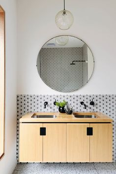 Bathroom with a retro pendant light, round mirror, and a floating vanity /
