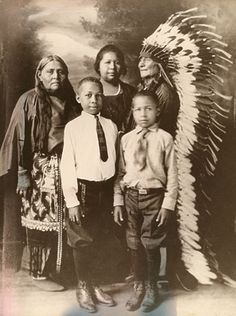 Comanche family, early 1900s from the Comanche Nation located in southwestern Oklahoma. The elder man in Comanche traditional clothing is Ta-Ten-e-quer. His wife, Ta-Tat-ty, also wears Comanche clothing. Their niece (center) is Wife-per, also known as Frances E. Wright. Her father was a Buffalo Soldier (an Afro American cavalryman) who deserted and married into the Comanches. Henry (center left) and Lorenzano (center right) are the sons of Frances, who married an Afro American man.