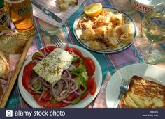 Download this stock image: Greek salad,calamares and saganaki served 'alfresco' - B0E6E6 from Alamy's library of millions of high resolution stock photos, illustrations and vectors.