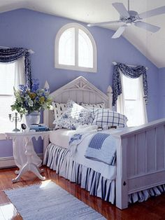 Who wouldn't want to take an afternoon snooze in this room? The guest bedroom is a serenade in blue — from floral window swags to the mismatched pillowcases.