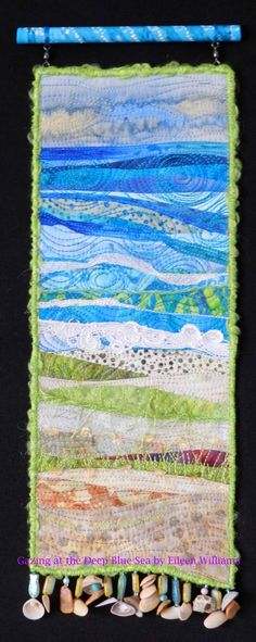 Gazing at the Deep Blue Sea.  Small art quilt by Eileen Williams.  Hanging from a painted dowel.  Embellished with found shells from the beach at Bear Island, N.C.