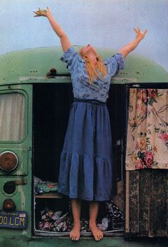 """One of the """"bus people"""" around Santa Cruz celebrates the day from the door of her home - a repainted and refurbished school bus. When police move in to enforce camping regulations, the beach squatters must move on. America's Sunset Coast  National Geographic Society ©1978"""