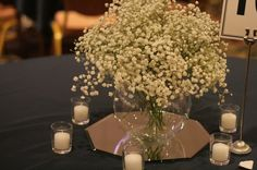 babys breath centerpiece in fish bowl. round table = round bowl?  or square vase?  make sure flowers are full enough so fish can't jump out.