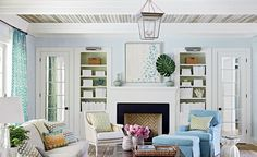 Light blue living room - love the art above the fireplace and the decorated shelves.