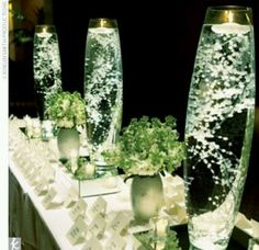 """Half the centerpieces - 24"""" cylinders w submerged baby's breath to add height to the space. Use same aqua sea glass and led light to tie into short centerpieces."""