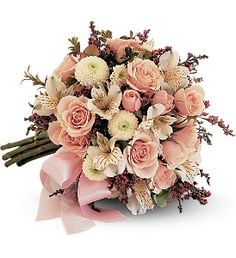 The hand-tied nosegay features pink spray roses, alstroemeria, button chrysanthemums, hydrangea and oregonia, with two types of pink ribbon.