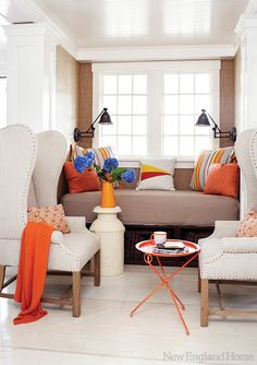 Cozy and relaxing window seat. Great place to curl up with a book! Adjustable wall reading lights and white windows and accent wing chairs.