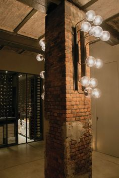 A wall sconce, outfitted with halogen lamps, glass globe shades, and a metal armature is affixed to a brick column outside the wine cellar.