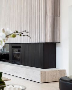 Travertine and limed white timber battens frame the fireplace at the Mornington Peninsula beach house. Beautifully captured by @arorygardiner