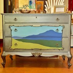 Artist Shannon Kae found this vintage dresser at Harrington galleries in San Francisco. Originally dark brown, she painted the body black and panel gray blue, then scrubbed on several layers of Smoke and Pale Gold Metallic Paints by Modern Masters for a rich warm lustre. She added her signature torn landscape motif for a stylized update on a classic treatment for this era dresser.