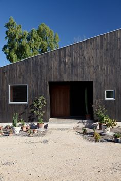Dark timber exterior cladding and minimalist desert garden with strong entry. Perfect.