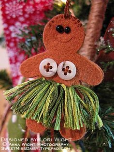 Hula Gingerbread Girl. Cut out two body shapes from brown felt. Do a short row of blanket stitching for hair, and embellish the body with two mother of pearl buttons, green embroidery floss for the skirt, and two beads for eyes.